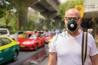 Senior man using face mask to protect from pollution smog in city