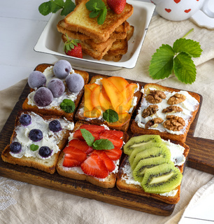 toasts with soft cheese, strawberries, kiwi, walnuts, cherries and blueberries