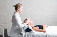 Professional female masseur giving relaxing massage treatment to young female client. Hands of masseuse on forehead of young lady during procedure of spa facial massage