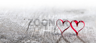 Red ribbon hearts on wood