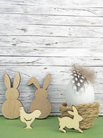 Easter background with Easter egg, Easter bunnies  and cock isolated on green in front of wood