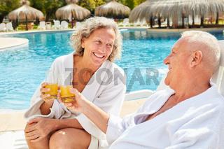 Paar Senioren mit Orangensaft am Spa Pool