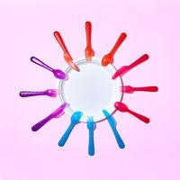 Multicolored plastic utensil around white plate on pink.