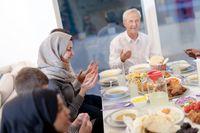 modern multiethnic muslim family praying before having iftar dinner