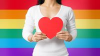 woman with gay awareness wristband holding heart