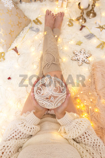 Female holds a glittering bauble among Chrismas decorations