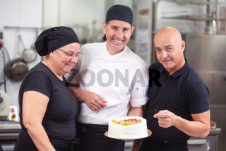 Smiling pastry Chefs showing a cake