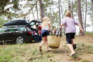 Kinder laufen mit einer Tasche zum Auto