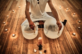 Young Man playing crystal bowls as part of a meditative concert