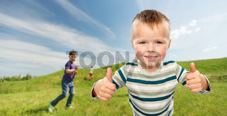 smiling boy showing thumbs up outdoors