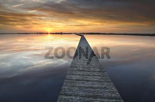 long walkway on big lake at sunset