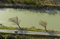 View from above on a car on a country road by a river, Rhone river near Martigny, Valais,Switzerland