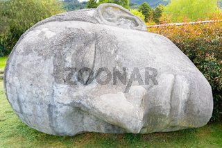 Colombia Tabio face carved in stone lying in the meadow close up