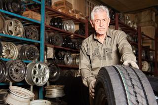 KFZ Mechaniker mit einem neuen Auto Reifen