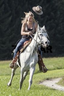 Junge Frau mit Cowboyhut  galoppiert auf ihrer Araberstute