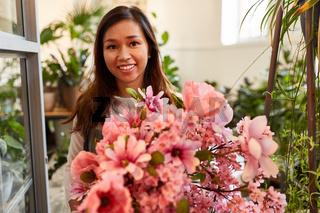 Floristin mit rosa Blumenstrauß zum Muttertag