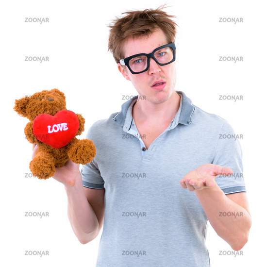 Funny young nerd man with big eyeglasses holding teddy bear and looking confused