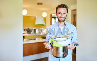 Hausmann in der Küche beim Geschirr aufräumen