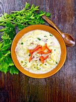 Soup creamy of chicken and pasta with pepper in plate on board top
