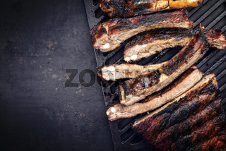 Barbecue spare ribs St Louis cut with hot honey chili marinade sliced as top view on grillage with copy space left