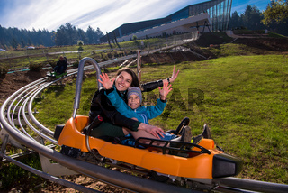 young mother and son driving alpine coaster