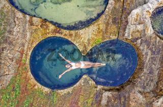 Female floating in idyllic ocean rock pool just bliss