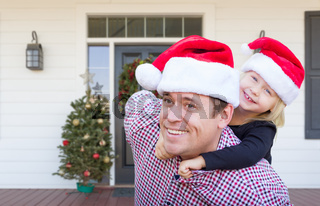 Young Father and Daughter Wearing Santa Hats On Front Porch of House With Christmas Decorations