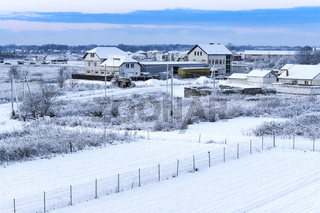 houses and fields covered with snow, rural landscape in winter