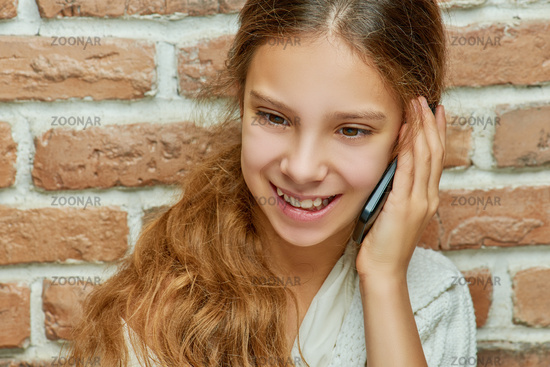 Smiling teen girl with long hair is talking on mobile phone