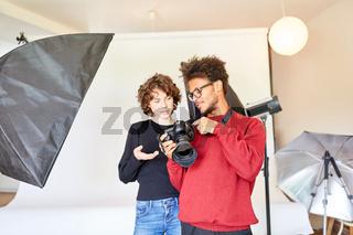 Fotograf und  Fotoassistent schauen auf Kamera