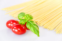 Uncooked pasta spaghetti, red tasty tomatoes and green basil leaves on white table