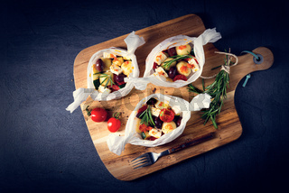 baked small dumplings with zucchini tomatoes and diced sheep's cheese