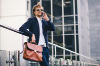 A Nice-Looking Male Boss In Formal Suit And A Briefcase In His Hand Is Smiling While Talking On The Phone In The Street