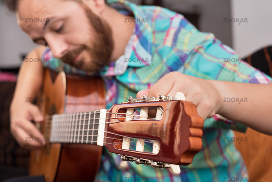 Bearded hipster man hand adjusting acoustic guitar. Close-up selective focus on hand.