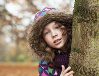 Teenager girl poking around a tree