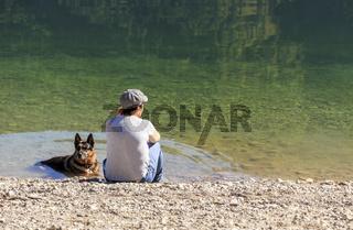 Badender Hund mit Frau am Seeufer