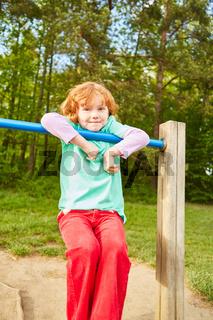 Mädchen spielt und klettert auf einem Klettergerüst