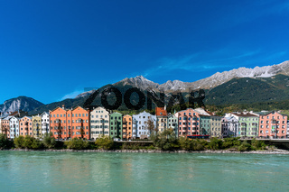 Colourful buildings in the austrian town Innsbruck with the river Inn and mountains in the background