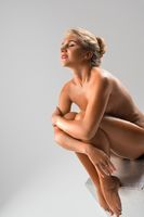 Nude blonde sitting on the cube view