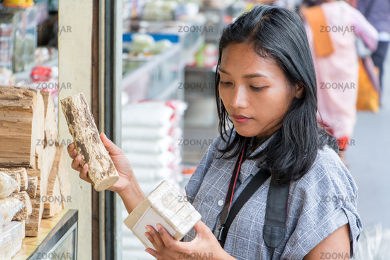 Asian woman chooses thanakha at the market.