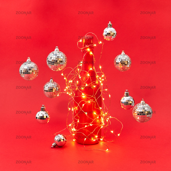 Wine bottle painted red covered garland with lights and flying balls.