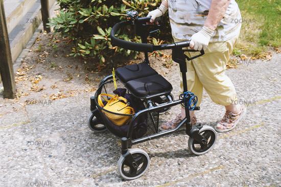 elderly woman walking outside with rollator or wheeled walker