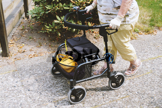 elderly woman walking outside with rollator or wheeled walker