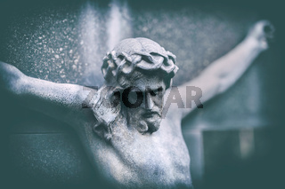 portrait of a weathered jesus on tombstone