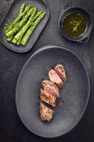 Fried Iberian pork fillet sliced with blanched green asparagus and butter sauce with spice as top view in a cast iron design plate