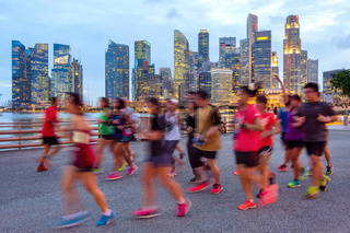 Joggers on illuminated Singapore promenade