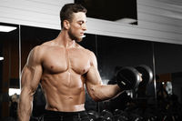 Muscular man working out in gym doing exercises with dumbbells