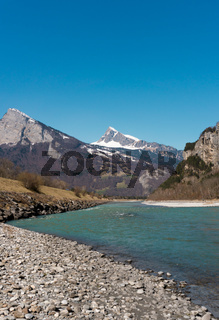 clear wide mountain river with snow-capped peaks behind under a clear blue sky
