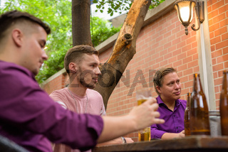 Group of men outdoors sitting and drinking beer