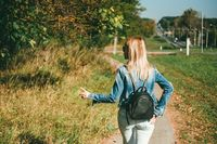 Slender blonde girl, in a blue denim jacket and light jeans and with a black leather backpack walks down the road against the backdrop of the autumn forest and highway. View from behind. Her fingers show a sign of victory